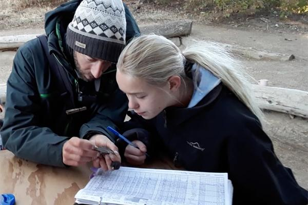 researcher shows a student how to band a songbird
