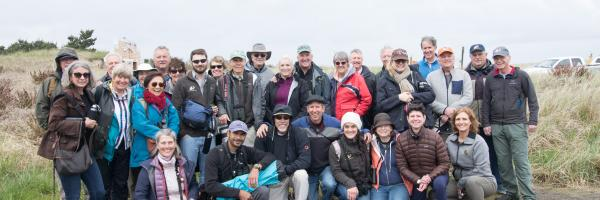 A large group photo of The Peregrine Fund's Board of Directors bird watching at Long Beach, Washington